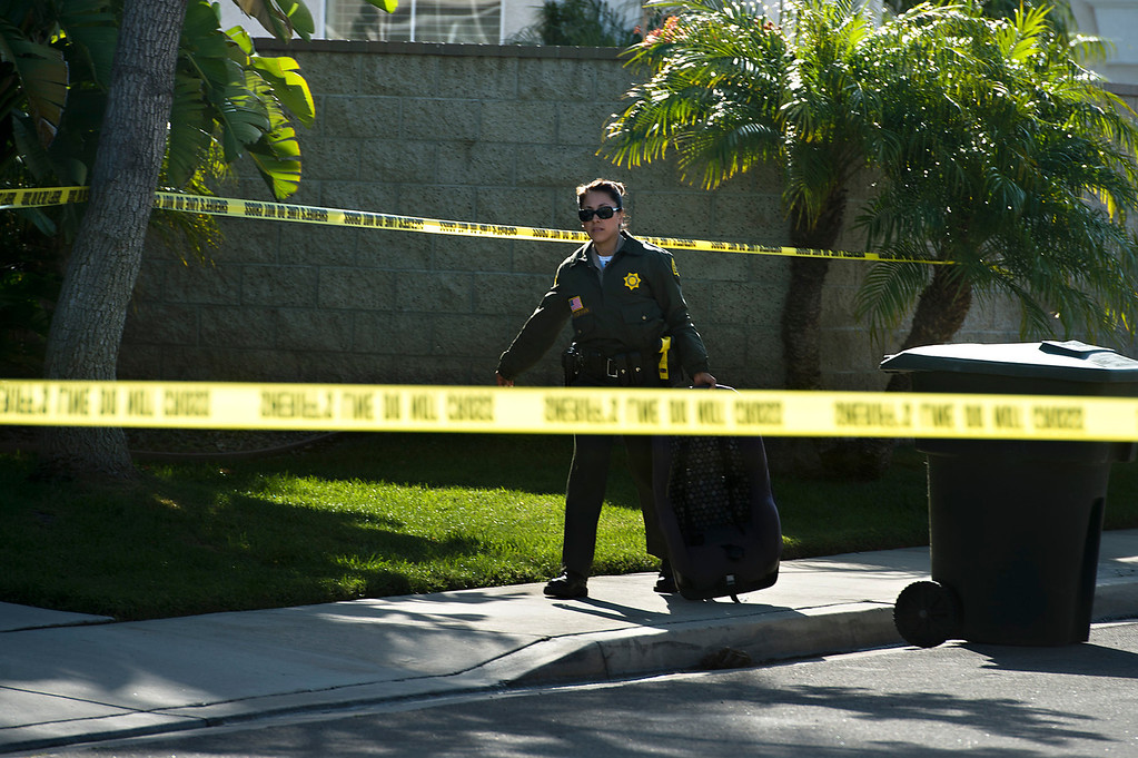Description of . A San Bernardino County sheriff's deputy walks exits the crime scene carrying a baby car seat after a fatal deputy-involved shooting in 5400 block of Brushwood Court in Chino Hills on Friday, March 28, 2014. f(Photo by Watchara Phomicinda/ San Gabriel Valley Tribune)