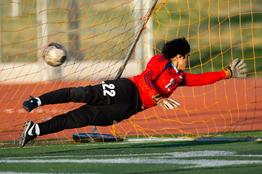 Description of . South Pasadena goal keeper Kevin Foster (22) dives to block a goal from Monrovia's Joel Cortez (21) in the second half of Boys soccer, South Pasadena at Monrovia on Wednesday, Jan. 8, 2013. Monrovia won 5-1. (Photo by Watchara Phomicinda/ Pasadena Star-News)