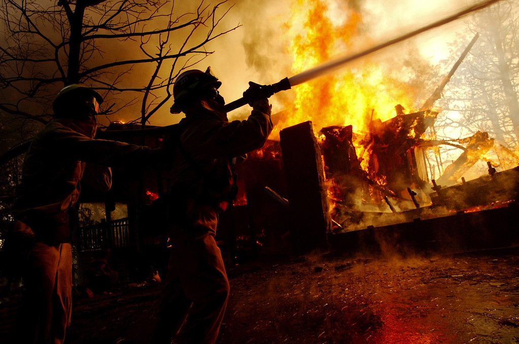 Description of . Ten years ago this month the arson caused Old Fire, fanned by Santa Ana winds burned thousands of acres, destroyed hundreds of homes and caused six deaths. The fire burned homes in San Bernardino, Highland, Cedar Glen, Crestline, Running Springs and Lake Arrowhead and forced the evacuation of thousand of residents. Firefighters fight a blaze at a home in Crestline, and try to stop the fire from spreading to the trees in the wilderness Sunday October 26, 2003 during the second day of the Old Fire. (Staff file photo/The Sun)