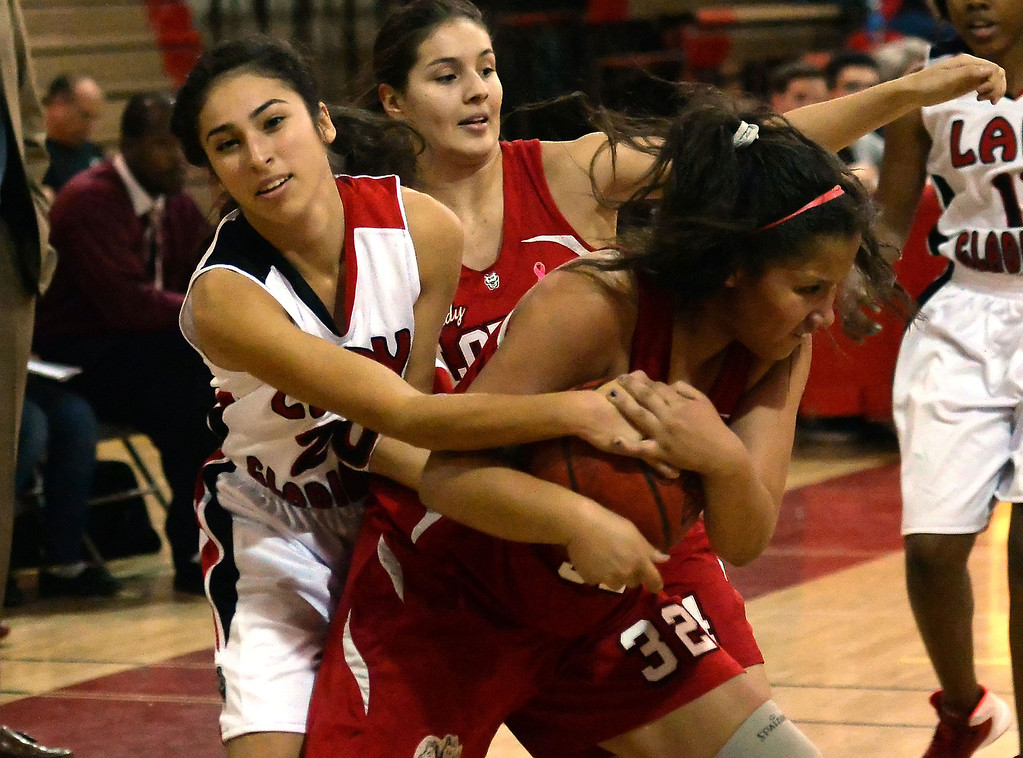 Description of . Workman's Alize Williams (32) fights for the ball with Gladstone's Jessica Rosas (C) (20) in the first half of a prep basketball game at Gladstone High School in Covina, Calif., on Friday, Jan. 17, 2014. (Keith Birmingham Pasadena Star-News)