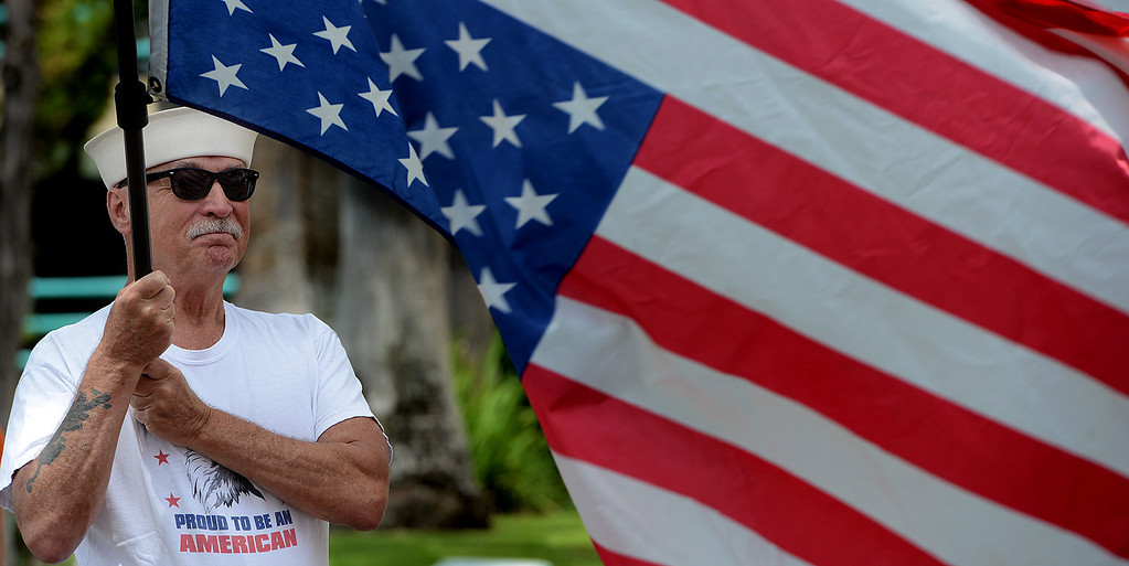 Description of . Ken Dalton, 74, of San Dimas waves an upside down American flag in response to what he says is,