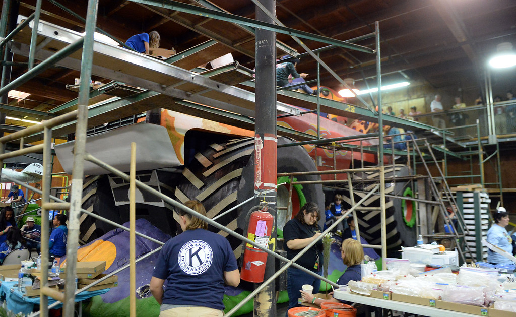 Description of . Volunteers work on floats during the final stages of preparation for the 2014 Rose Parade as a variety of seeds, bark, fruits and vegetables, grasses and of course, flowers are being applied to the floats by experienced professionals as well as hard working volunteers at the Rosemont Pavilion in Pasadena, Calif., on Saturday, Dec. 28, 2013.     (Keith Birmingham Pasadena Star-News)