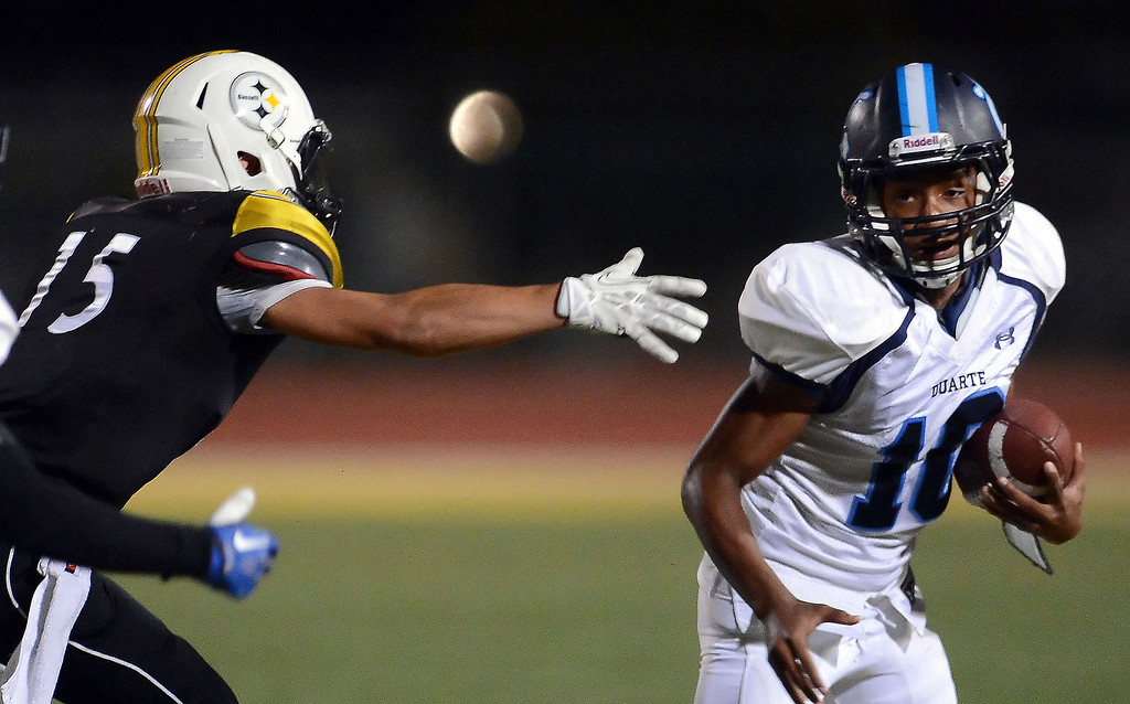 Description of . Duarte's Kamar Watson (10) runs for a first down past Bassett's Eric Ruff (15) in the first half of a prep football game at Bassett High School in La Puente, Calif., on Friday, Nov. 1, 2013.    (Keith Birmingham Pasadena Star-News)