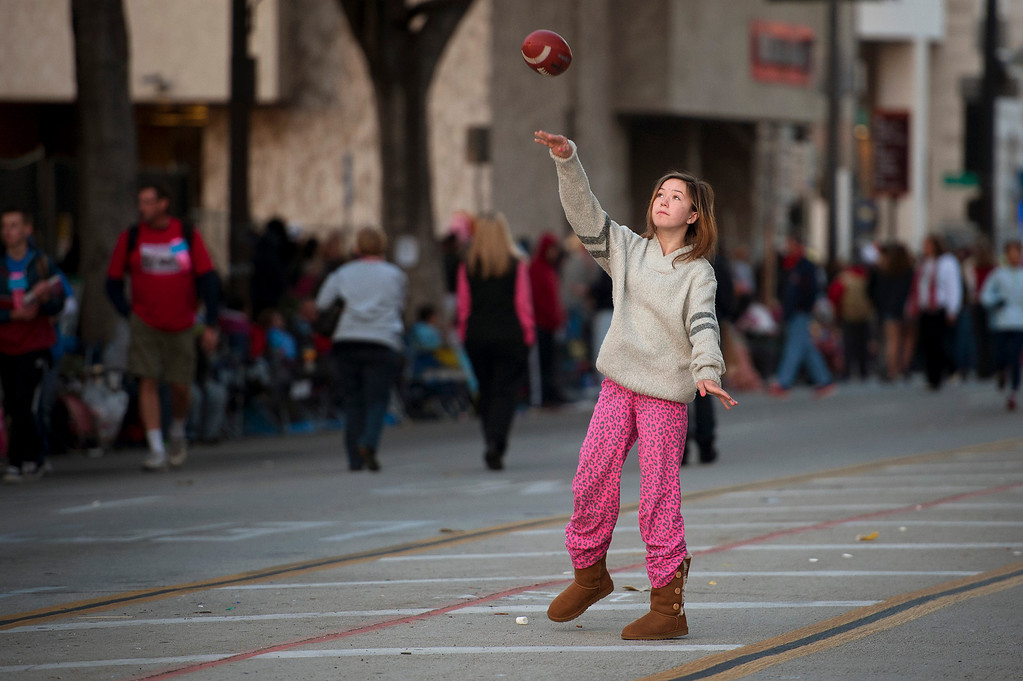 Description of . Ariel Anderson throws a football on Colorado Blvd. while waiting for the start of the 2014 Rose Parade in Pasadena, CA January 1, 2014.(Andy Holzman/Los Angeles Daily News)