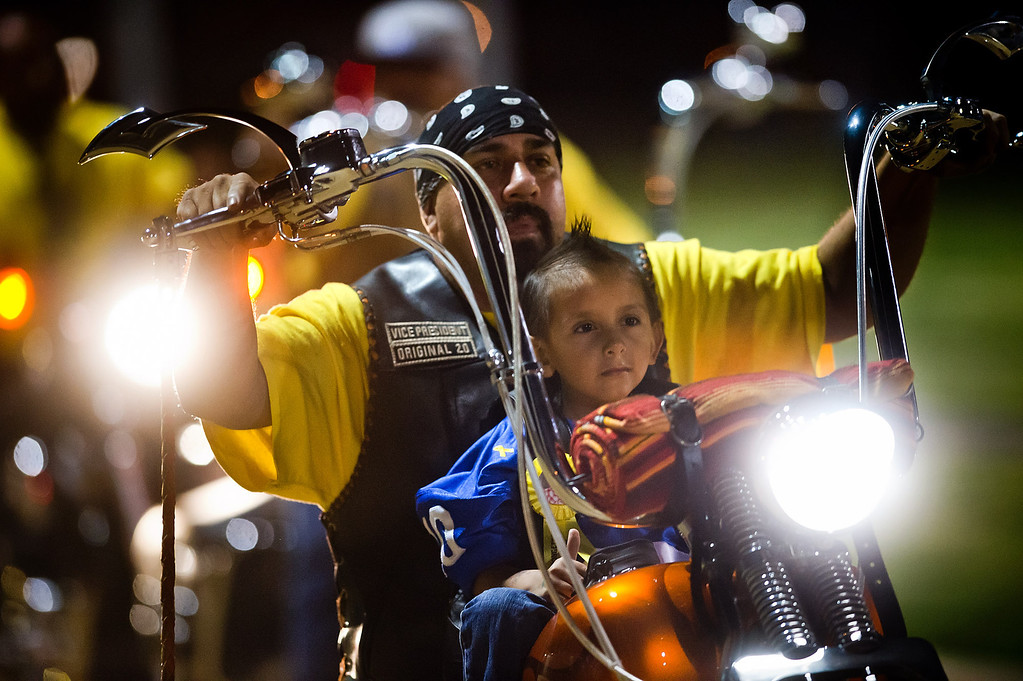 Description of . Doryan Torres, 5, rides with Eirc Montano, of La Puente, as he is presented during the El Monte High School football halftime special in El Monte on Friday night, Sept. 13, 2013. Torres who is turning 6 on Saturday, has been battling a brain tumor since he was 14 months old. (Photo by Watchara Phomicinda/ San Gabriel Valley Tribune)