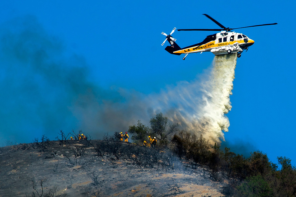 Description of . LA County Fire helicopter makes a water drop along a ridge near Big Dalton in Glendora, Calif. on Thursday, Jan. 16, 2014. (Photo by Watchara Phomicinda/ San Gabriel Valley Tribune)