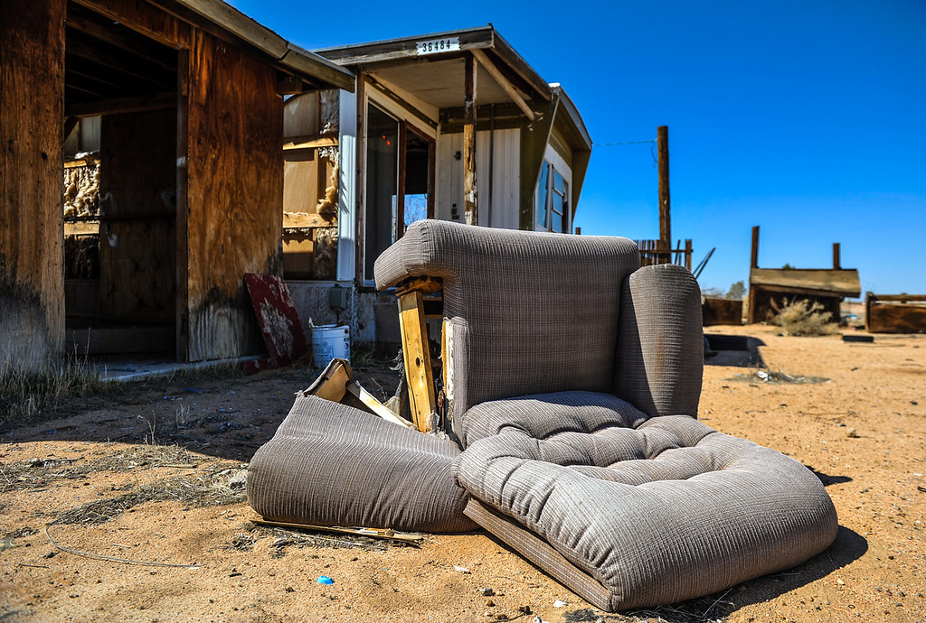 Description of . A chair and other furniture items are left outside an abandoned home on the 36000 block of Mountain View Road in Hinkley, Calif. on Saturday, March 16, 2013. In the last two years, residents have become aware that a toxic water plume continues to grow below their small town, some have moved out of Hinkley. (Rachel Luna / San Bernardino Sun)
