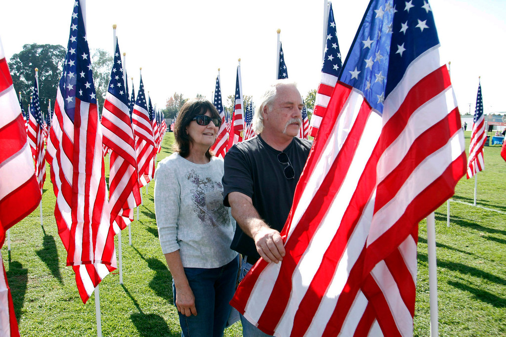 Description of . U.S. Navy Veteran, Ronald Ray Bergstrom and his wife Sharon Bergstrom, of LA Verne, stand next to the flag dedicated him, during the opening ceremony for the Field of Valor, where 2,027 flags are posted in honor of Veterans Day, at the Field of Valor at Sierra Vista Middle School in Covina, CA., Sunday, November 10, 2013. (Photo by James Carbone for the San Gabriel Valley Tribune)