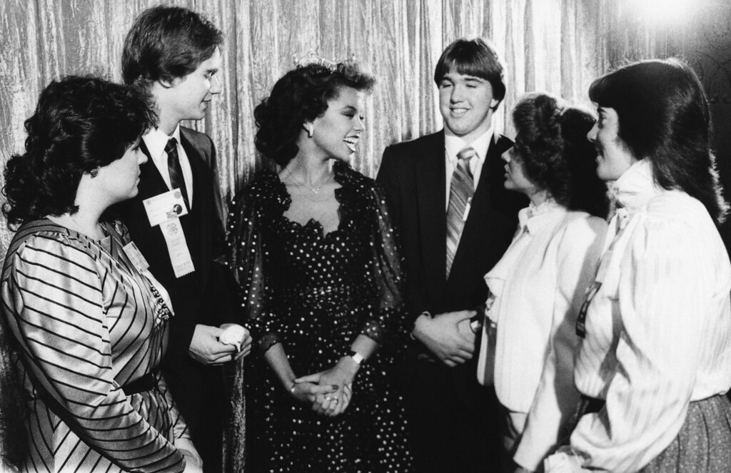 Description of . Vanessa Williams, Miss America, talks with 4-H delegates before speaking at a luncheon at the 62nd National 4-H Congress in Chicago, Nov. 30, 1983. The delegates from left to right are: Lisa Hutchins, Bowman, S.C.; Mike Young, Farmingdale, N.Y.; Williams, Doug Bowman, Jenkins, Mo.; Dorinda Roberts, Riceville, Tenn.; Lisa Clement, Bucksport, Maine. (AP Photo/Charles Knoblock)