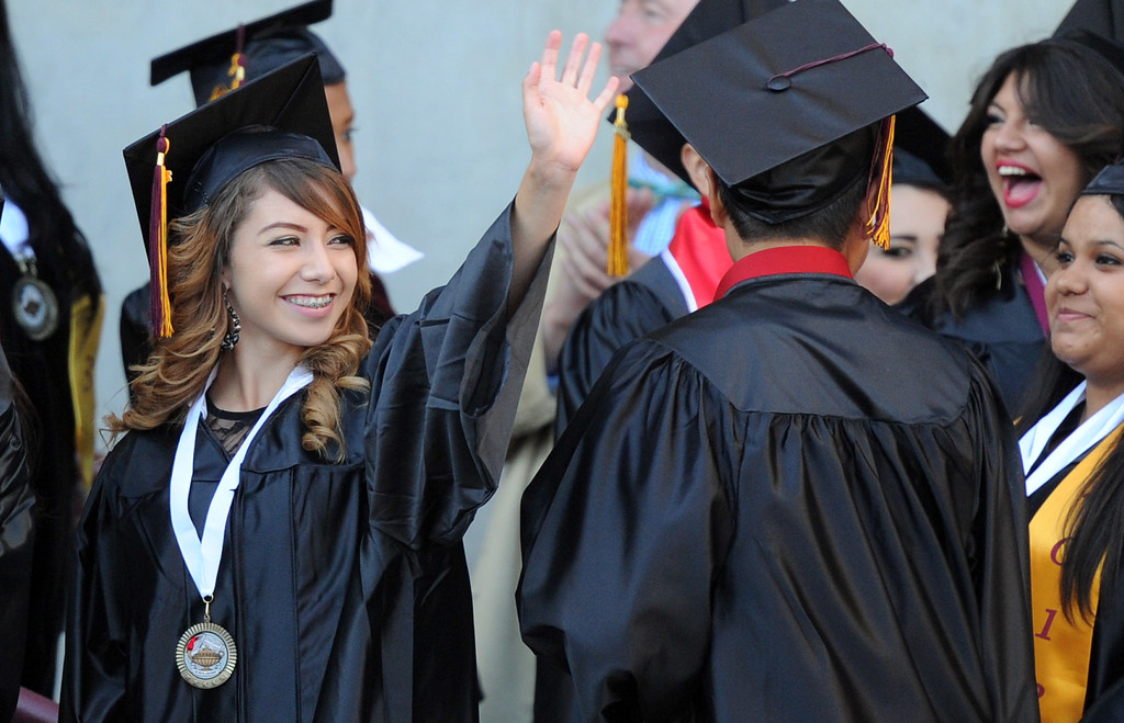Description of . A student waves to family and friends during the Vail High School commencement at Vail High School on Tuesday, June 18, 2013 in Montebello, Calif.