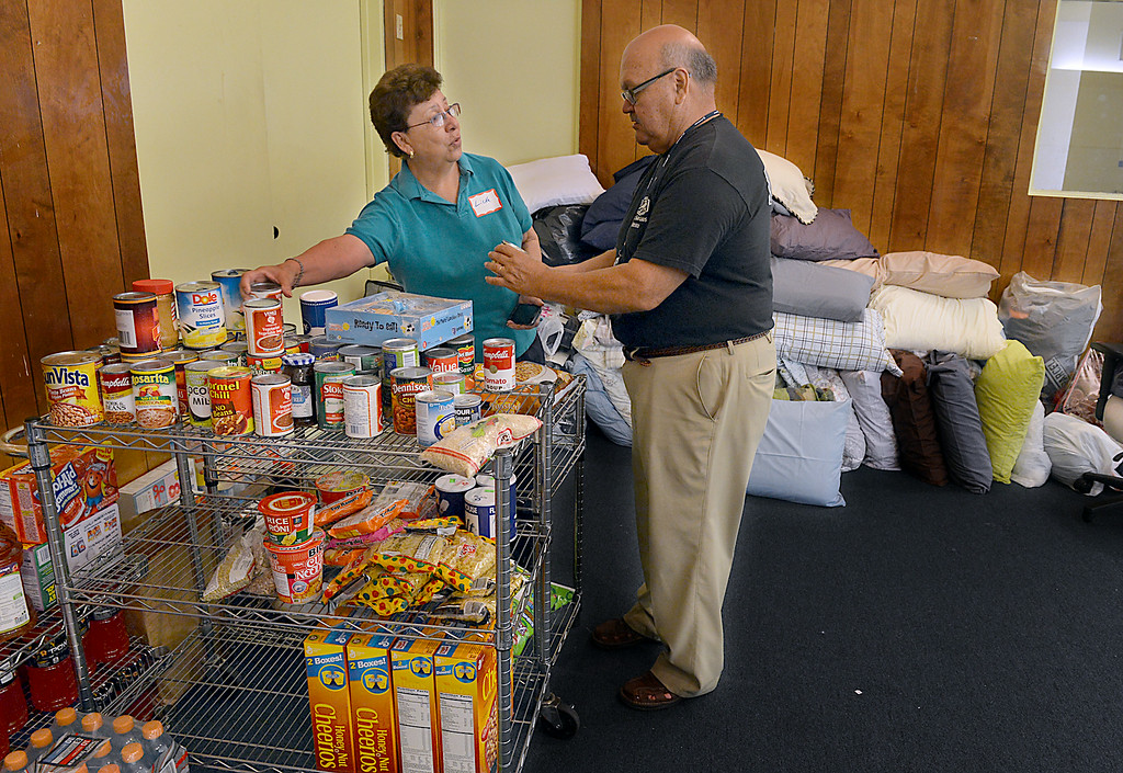 Description of . Lietta and Gonzalo Sotelo go through donated food and bedding at St Catherine of Siena in Rialto. Gonzalo Sotel, a deacon at the church says they are ready to help immigrant children and families. A Fontana church, St. Joseph's Catholic Church, is caring for a group of immigrants from Central America, and volunteers at two other Inland churches, including St. Catherine of Siena, are making preparations to help. A bus transported 46 immigrants, mostly children, this morning Thursday July 10, 2014 to St. Joseph's. (Photo by Rick Sforza/The Sun)