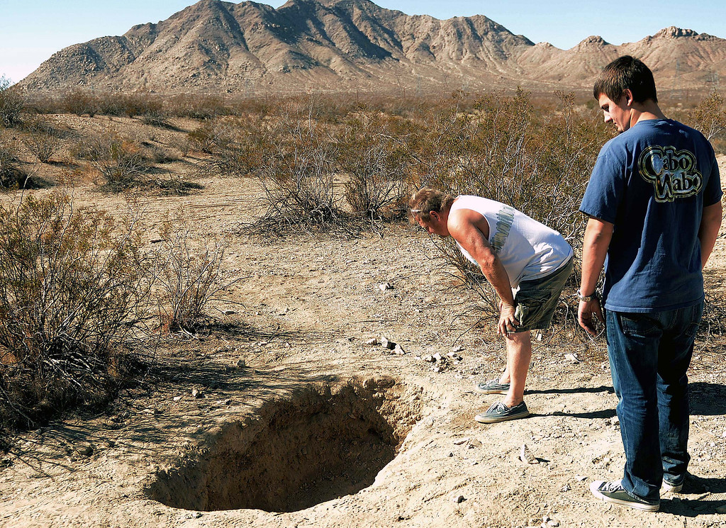 Description of . Joel Myers,51, left, and Allen Gadban,20 both of Adelanto looks at the hole Thursday November 14, 2013 where skeletal remains were found in shallow graves Tuesday November 12, near Victorville.The multiple grave sites were found west of the 15 Freeway. LaFonzo Carter/ Staff Photographer