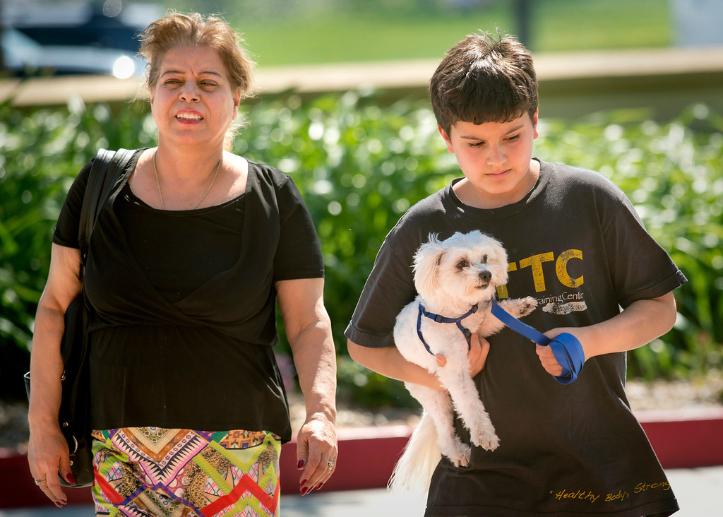 Description of . Patrick Acs, 12, arrives carrying the family dog, accompanied by his mother Nahid, at the Goldy S. Lewis Community Center in Rancho Cucamonga, Calif. after being displaced from their Rancho Cucamonga home by the Etiwanda Fire April 30, 2014.  (Staff photo by Leo Jarzomb/San Gabriel Valley Tribune)