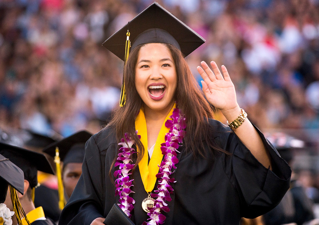 Description of . Connie Nguyen waves to family in the stands during Northview High graduation commencement at Covina District Field June 11, 2014.   (Staff photo by Leo Jarzomb/San Gabriel Valley Tribune)