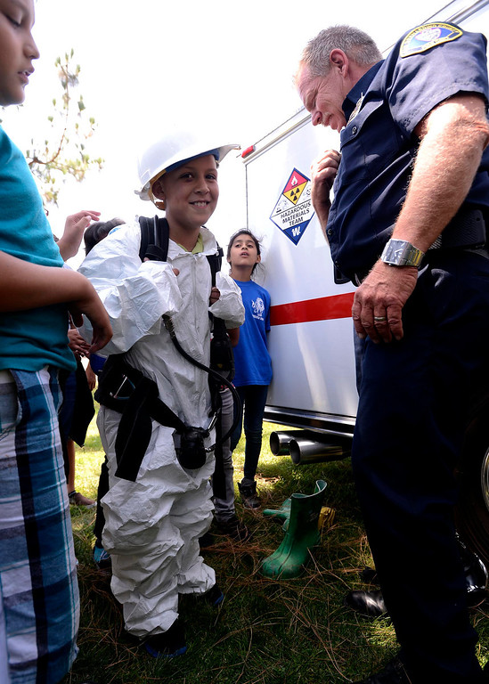 Description of . Brian Otter of San Bernardino County Fire/ Hazardous Material, right,  outfits fourth grader Donovan Barajas with Hazmat suit during the final day of the 19th Annual Career Awareness Week at Lankershim Elementary School in Highland June 6, 2013.  GABRIEL LUIS ACOSTA/STAFF PHOTOGRAPHER.