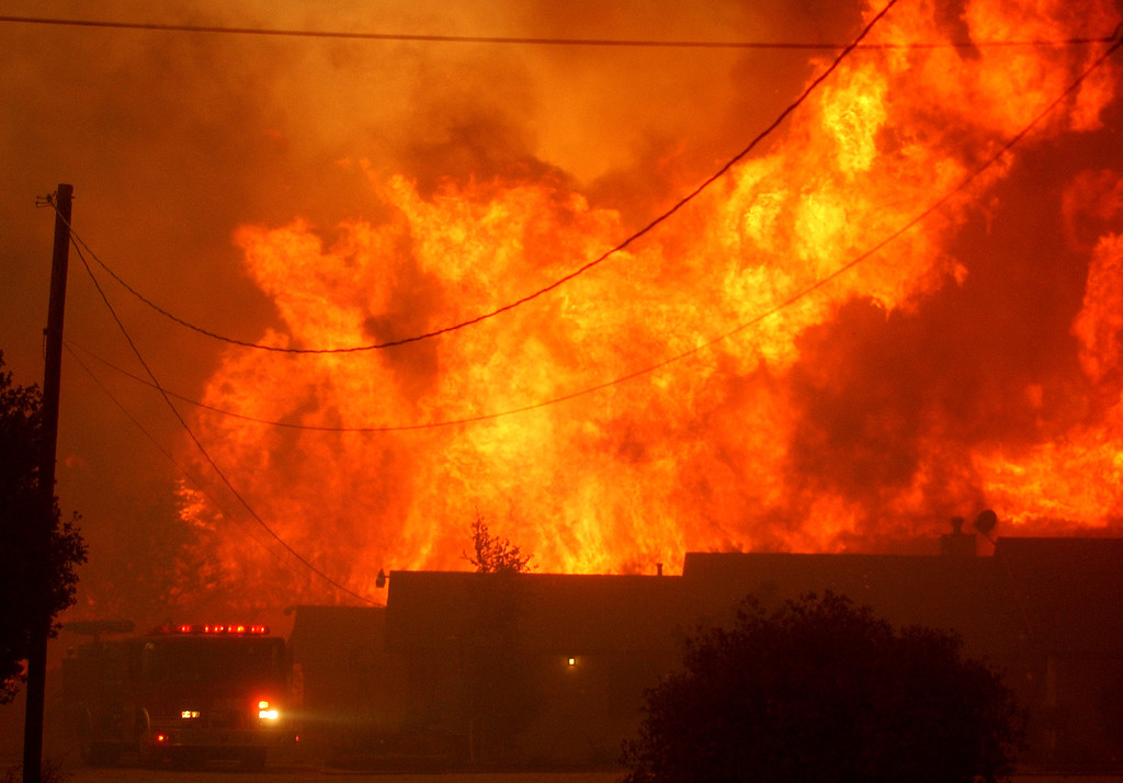 Description of . Ten years ago this month the arson caused Old Fire, fanned by Santa Ana winds burned thousands of acres, destroyed hundreds of homes and caused six deaths. The fire burned homes in San Bernardino, Highland, Cedar Glen, Crestline, Running Springs and Lake Arrowhead and forced the evacuation of thousand of residents. Santa Ana City Fire crews make a stand at John Biery's Summit Valley, home along Highway 138 Wednesday, Oct. 29th 2003 during the