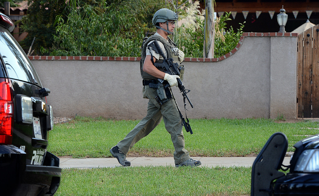 Description of . More than a dozen federal agents in body armor and other law enforcement officers raided a Redlands home Thursday morning as part of a gang investigation. The FBI gathered in the city at 5:12 a.m. and served a search warrant at a home in the 800 block of East High Avenue. Police took a man into custody at another location in the 400 block of Western Avenue in the city. (Photo by Rick Sforza/Redlands Daily Facts)