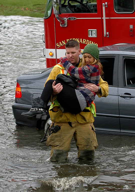 Description of . San Bernardino City firefighter paramedic Corie Lynch rescues Maegen Pettit, 25, of Ventura, from a vehicle that got stuck in the flooded intersecion of Hosptiality Lane and E Street in San Bernardino March 17, 2012.  The flooding was caused by a drain overflowing due to an extreme deluge of rain.  (Photo by Gabriel Luis Acosta/The Sun)