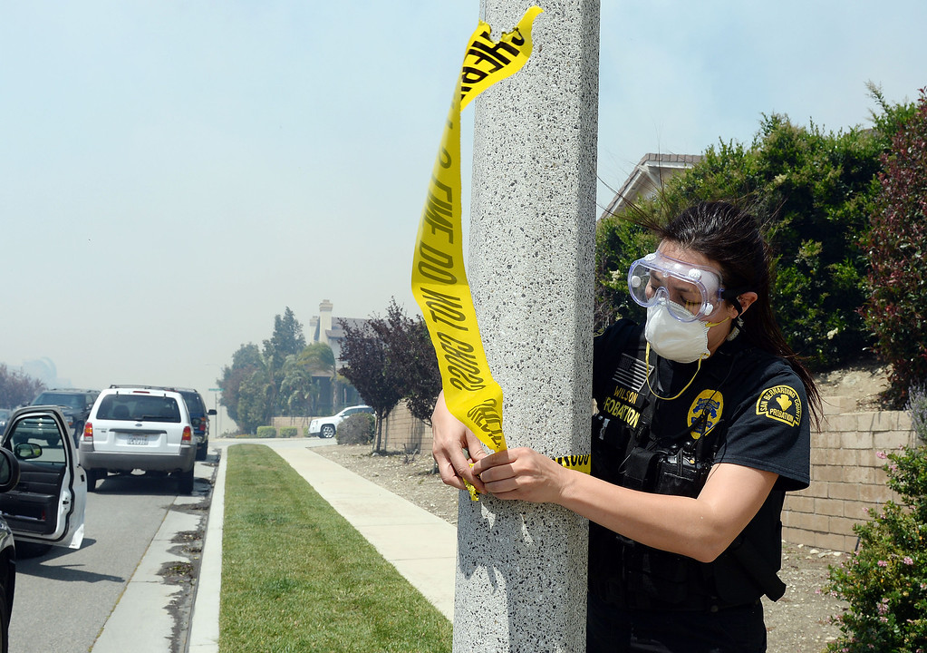 Description of . A San Bernardino Sheriffs deputy ties tape to a flag pole to show the street is under mandatory evacuations during the Etiwanda Fire Wednesday in Rancho Cucamonga. Over 1000 acres and over a 1,000 homes are under mandatory evacuation as the Etiwanda Fire burns in Rancho Cucamonga Wednesday April 30, 2014. Cause of the fire is unknown and is burning in areas which burned during the Grand Prix Fire in October 2003. (Will Lester/Inland Valley Daily Bulletin)