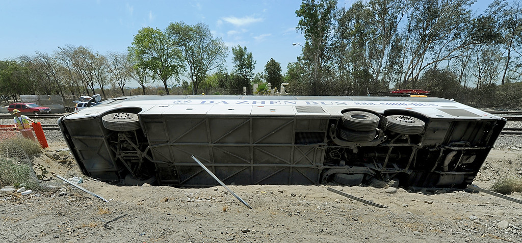 Description of . A tour bus on its way to an Indian Casino tangled with two other cars on the (210) freeway near Irwindale offramp, causing the bus to flip over on its side on the freeway embarkment Thursday, August 22, 2013.  Fifty-Five people were injured and five people were air-lifted by helicopters to trauma centers.  The cause of the bus accident is under investigation.(SGVN/Photo by Walt Mancini)