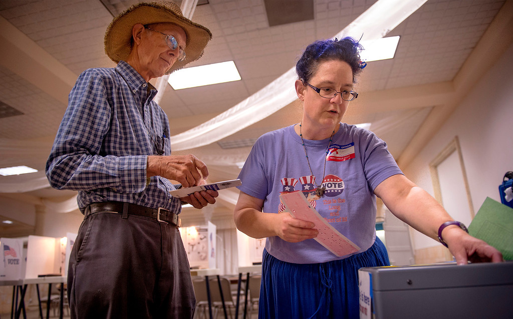 Description of . Polling inspector Lori Graham assists Whittier, Calif. voter Jonathan Vieg, 73, with his ballot and the voting machine at the Greenleaf Masonic Temple on Beverly Boulevard Tuesday morning June 3, 2014.   (Staff photo by Leo Jarzomb/Whittier Daily News)