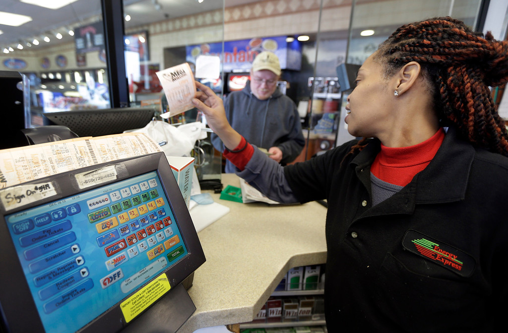 Description of . Energy Express assistant manager Anita Watson, right, sells a Mega Millions lottery ticket to Brian Thomason Monday, Dec. 16, 2013, in St. Louis. The Mega Millions jackpot soared to $586 million on Monday amid a frenzy of ticket purchases, a jump that pushed the prize closer to the $656 million U.S. record set last year. (AP Photo/Jeff Roberson)
