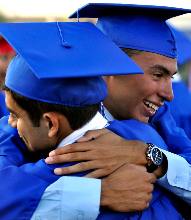 Description of . Graduates David Heredia, 18,  left and Christian Garcia, 17, congratulate one another.  Los Altos High School's 53 Commencement Ceremonies held in the Patrick Mauch Memorial Stadium, Tuesday, May 21, 2013.  (Correspondent photo/Mike Mullen)