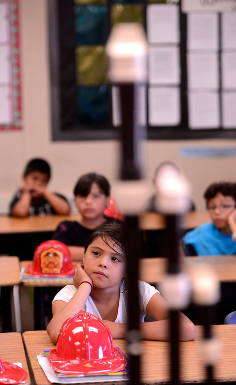Description of . Third grader Gyselle Charo, listens to musician Kim Hutchcroft, not pictured, speak about his instruments during the final day of the 19th Annual Career Awareness Week at Lankershim Elementary School in Highland June 6, 2013.  GABRIEL LUIS ACOSTA/STAFF PHOTOGRAPHER.