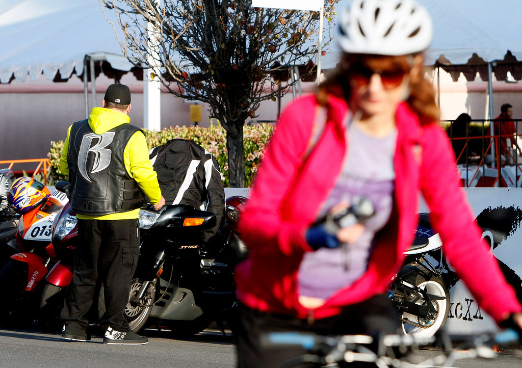 Description of . A member of the Ruff Riders Motorcycle Club, left, is seen as a female cyclist warms up for the R.U.F.F Ride during the public race portion of the Redlands Bicycle Classic on Saturday, April 5, 2014 in Redlands, Ca. (Photo by Micah Escamilla for the Redlands Daily Facts)