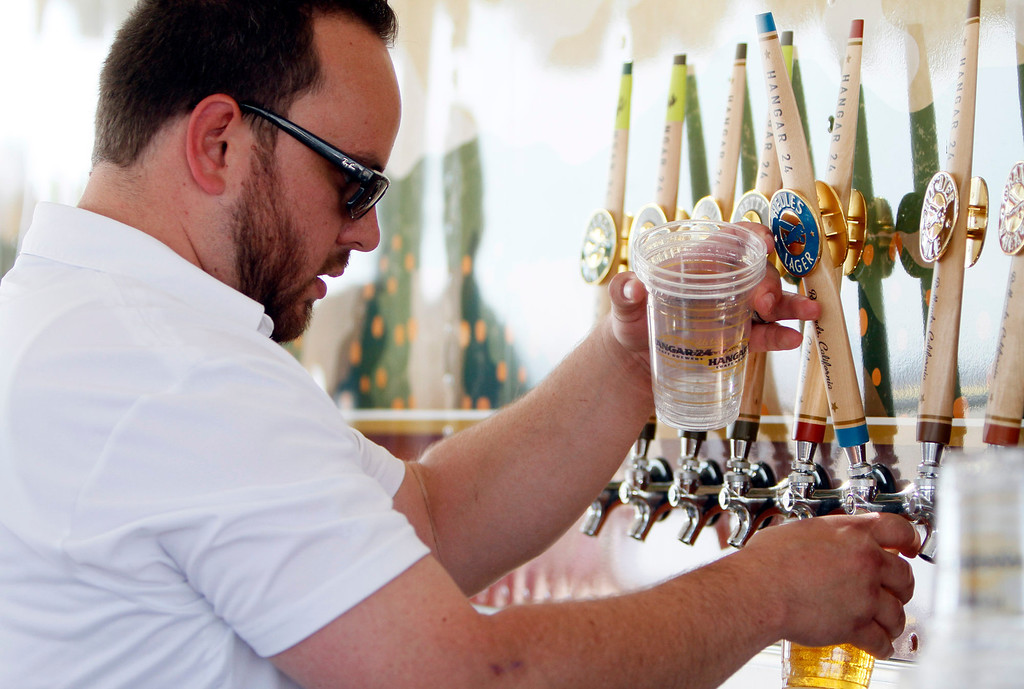 Description of . Hangar 24 sales representative Andrew Peterson pours a selection of beer during the Hangar 24 AirFest and 6th Anniversary Celebration on Friday, May 16, 2014 at the Redlands Municipal Airport in Redlands, Ca. (Photo by Micah Escamilla/Redlands Daily Facts)