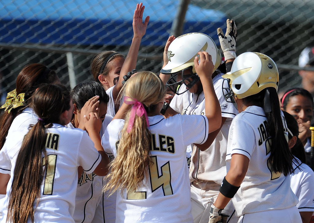 Description of . Northview's Jocelyn Marquez, center, is mobbed by teammates after hitting a solo home run in the sixth inning of a CIF-SS quarterfinal playoff softball game against Barstow at Northview High School on Thursday, May 23, 2013 in Covina, Calif. Northview won 5-4.  (Keith Birmingham Pasadena Star-News)