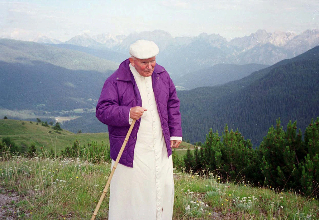 Description of . Pope John Paul II, wearing a violet wind jacket, walks in the Dolomite mountains in this Monday July 15, 1996 file photo provided by the Vatican. Abruzzo, a region in central Italy,  is renaming one of its peaks after Pope John Paul II, an avid skier and hiker who had a particular fondess for that area until frail health stopped him, the group that promoted the effort said Wednesday, March 23, 2005. The group plans to officially dedicate the  peak in the Abruzzo region on the pope's 85th birthday on May 18. (AP Photo/Vatican)
