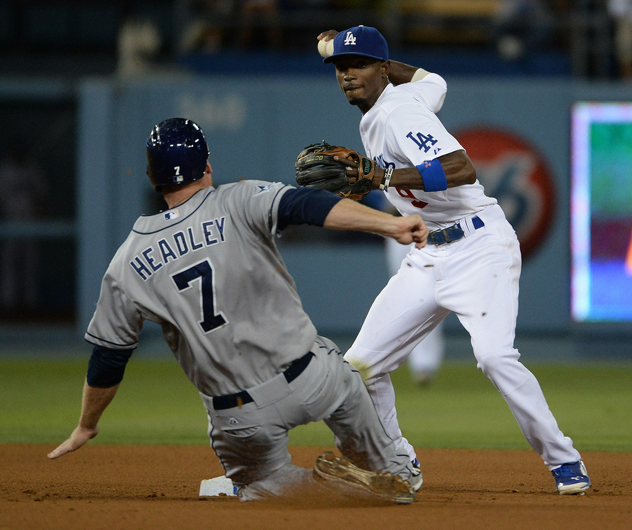 Description of . Los Angeles Dodgers second baseman Dee Gordon forces out San Diego Padres' Chase Headley (7) at second base as he throws to first to complete the double play on Carlos Quentin (not pictured) in the seventh inning of a Major league baseball game on Saturday, July 12, 2014 in Los Angeles.   (Keith Birmingham/Pasadena Star-News)