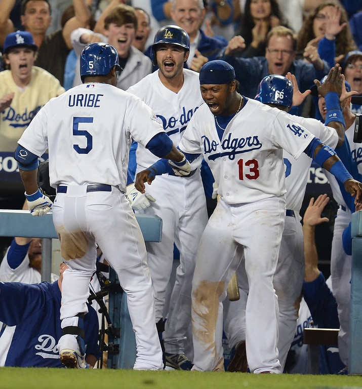 Description of . The Dodgers'  Juan Uribe is congratulated by Andre Ethier and Hanley Ramirez after his bottom of the 8th 2 run homer against the Atlanta Braves during game 4 of the NLDS at Dodger Stadium Monday, October 7, 2013. The Dodgers beat the Braves 4-3.(Photo by Hans Gutknecht/Los Angeles Daily News)