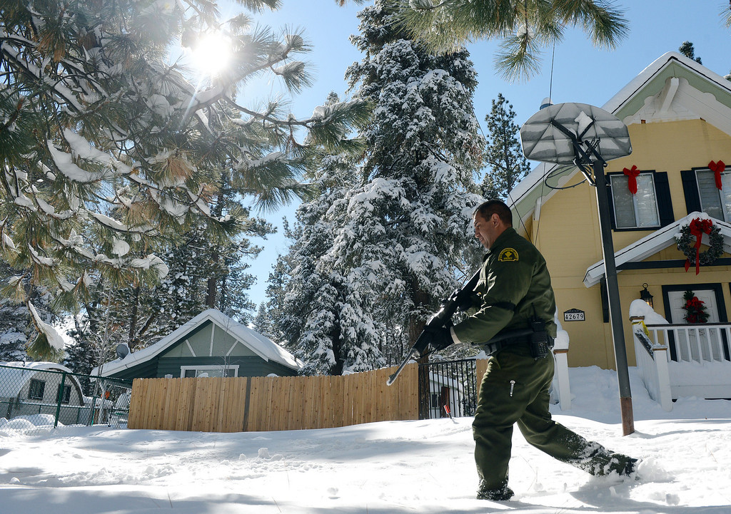 Description of . San Bernardino County Sheriff deputies continue to search door-to-door in Big Bear for ex-LAPD fugitive Christopher Jordan Dorner Saturday February 9, 2013. Search conditions improved Saturday as skies cleared in the area after a heavy winter storm dropped over a foot of snow in the mountain community Friday. (Staff photo by Will Lester/Inland Valley Daily Bulletin)