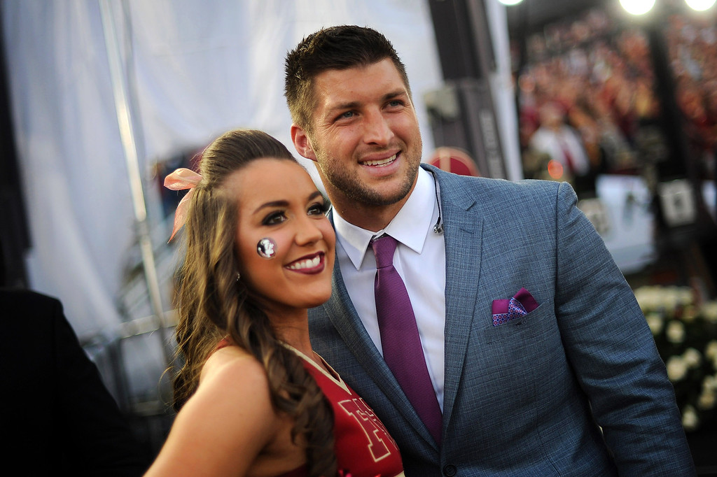 Description of . Tim Tebow poses for a photo with Florida State cheerleader Taylor Rone prior to the start of the 2014 Vizio BCS National Championship January 6, 2014 in Pasadena CA.(Andy Holzman/Los Angeles Daily News)