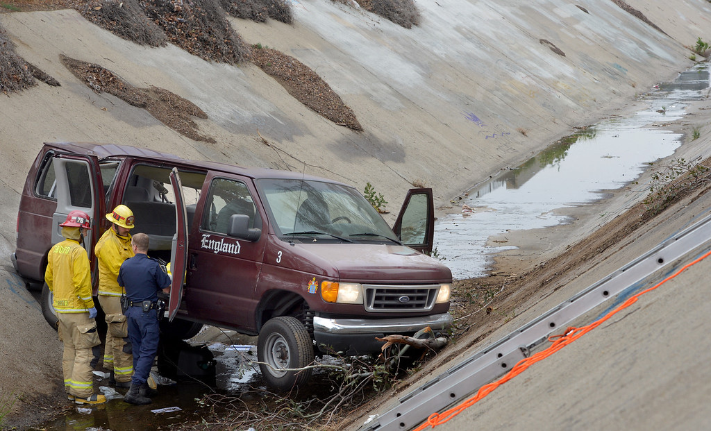"Description of . One person died and nine others were injured when a van plunged down the side of the 10 Freeway, in Bloomington, Thursday April 17, 2014. According to the CHP, the driver of the van apparently lost control of the vehical after hitting the brakes while approaching traffic. ""As the van left the freeway lanes, it struck a tree and began to overturn and eventually landed in a drainage ditch,"" said CHP Officer Leon Lopez. (Photo by Rick Sforza/The Sun)"