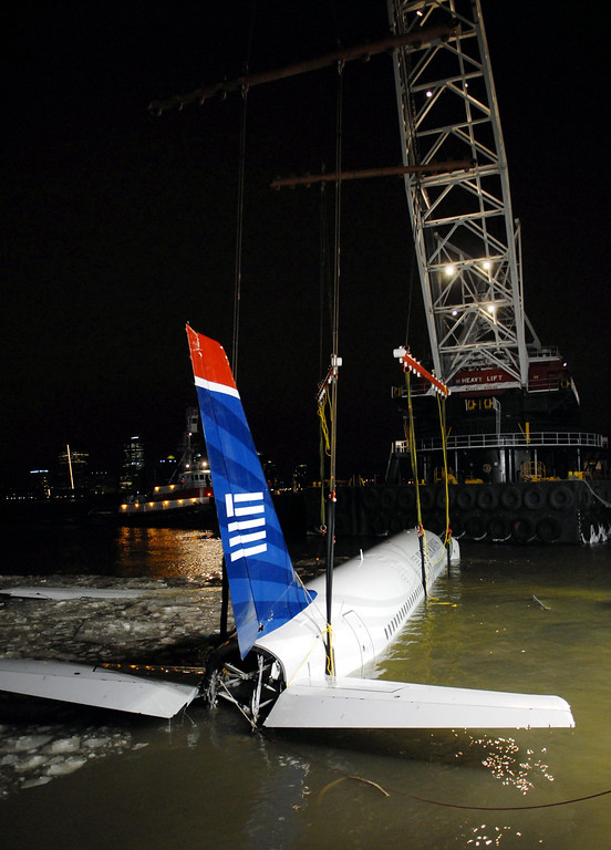 Description of . A heavy lift crane removes US Airways flight 1549 from its makeshift mooring along a seawall in lower Manhattan, Saturday, Jan. 17, 2009 in New York.  Investigators began interviewing the pilot, Chesley B.