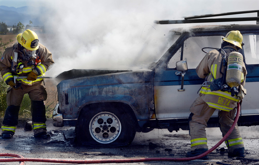 Description of . Ontario firefighters Danny Reza, right, and Tommy Pacheco battle a vehicle fire on the Vineyard offramp Thursday May 2, 2013. Marco Perez of Riverside said he smelled gas coming from his truck and pulled over to the shoulder of the Vineyard Avenue offramp of the westbound 10. No one was injured and the cause of the fire is under investigation. (Rick Sforza/Inland Valley Daily Bulletin)