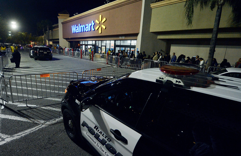 Description of . Rialto police vehicles sit outside a Rialto Walmart Thursday night November 28, 2013 after 3 seperate altercations took place at the store Thursday night. Police officers descended on Walmart in Rialto after a brawl between two men injured a police officer who tried to break up the fight Thursday night. The injured officer was transported to St. Bernardine Medical Center in San Bernardino with a broken wrist, police officials said. A Walmart manager said the doors were originally scheduled to open at 8 p.m. but with the more than 3,000 people in line they made the decision to open the doors early, which police said led to the melee. Police said there were three fights total shortly after 7 p.m. at the store at 1610 S. Riverside Ave., two of which were inside over merchandise and the third outside that caused injury to the officer. (Will Lester/Inland Valley Daily Bulletin)