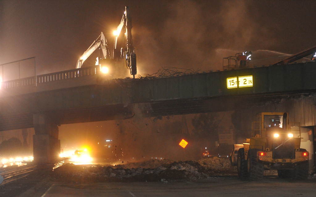 Description of . Loaders haul away debris as contractors work to demolish the Alondra Bridge over the Santa Ana  (I-5) Freeway early Saturday morning June 15, 2013. Traffic was closed on the northbound lanes as the surface of that side of the bridge is removed. The northbound steel girders are expected to be removed Sunday. (SGVN/Staff Photo by Keith Durflinger)