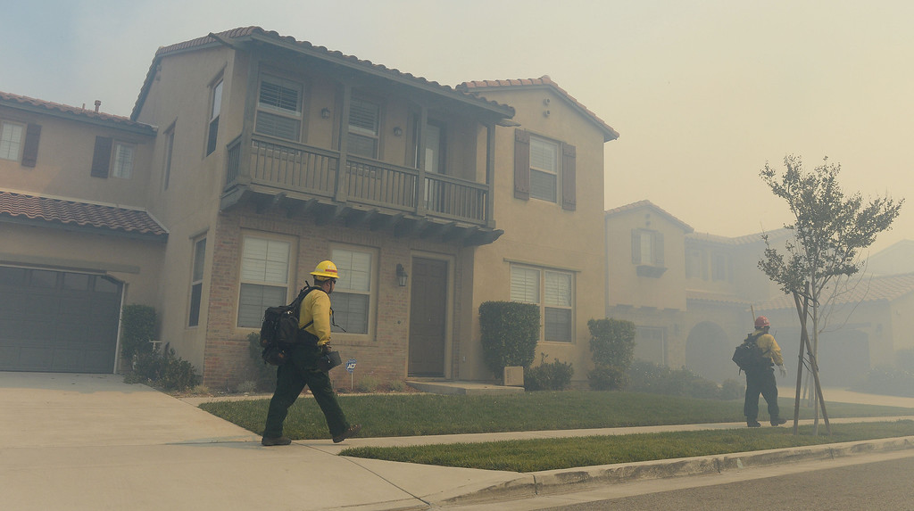 Description of . Firefighters walk a smoke filled street Wednesday in Rancho Cucamonga. Over 1,000 acres and over a 1,000 homes are under mandatory evacuation as the Etiwanda Fire burns in Rancho Cucamonga Wednesday April 30, 2014. Cause of the fire is unknown and is burning in areas which burned during the Grand Prix Fire in October 2003. (Will Lester/Inland Valley Daily Bulletin)