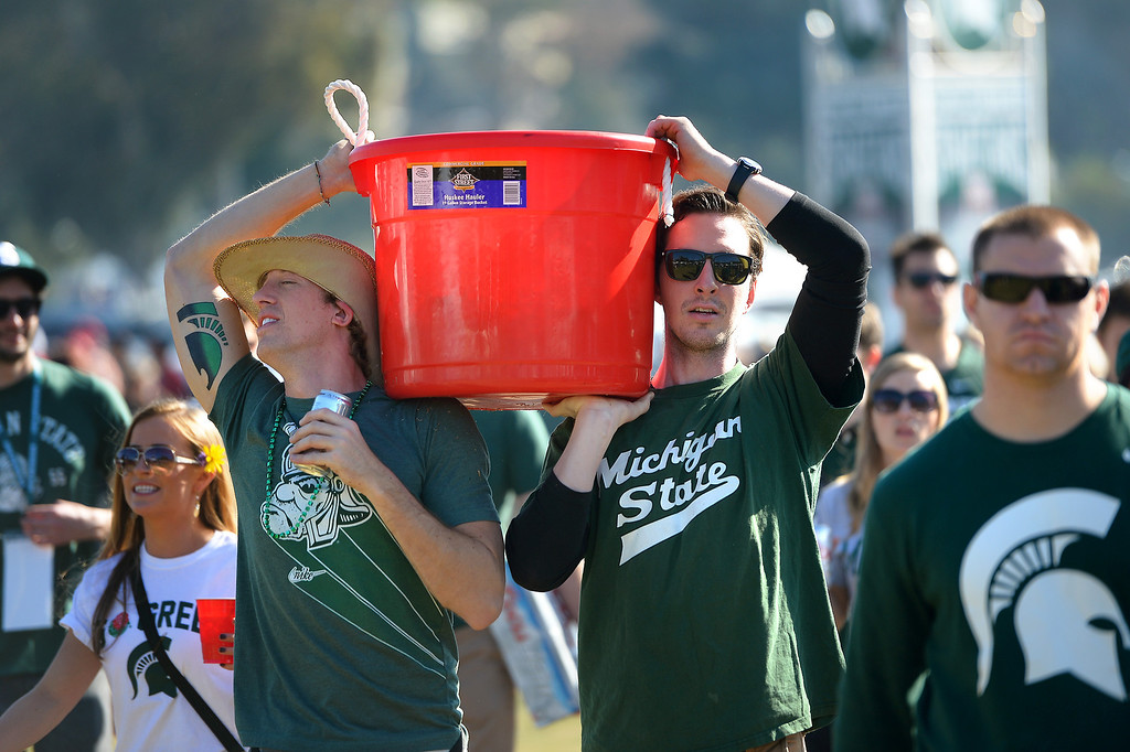 Description of . Michigan State fans carry a bucket of refreshments in front of the Rose Bowl before the game, Wednesday, January 1, 2014. (Photo by Michael Owen Baker/L.A. Daily News)