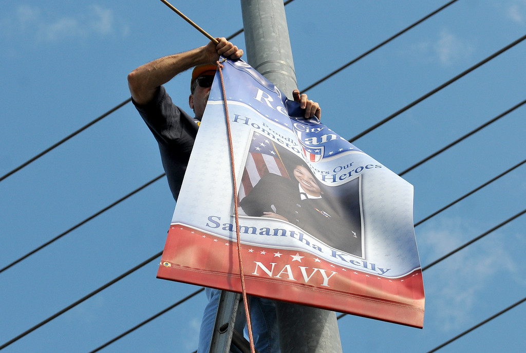 Description of . (John Valenzuela/Staff Photographer) Redlands Evening Kiwanis Club member Jerry Linkhart, hangs a Hometown Heroes banner for Redlands' Naval officer Samantha Kelly, at the corner of New Jersey St. and Redlands Blvd., Tuesday, August 27, 2013. Kelly is a 2006 Redlands East Valley grad.