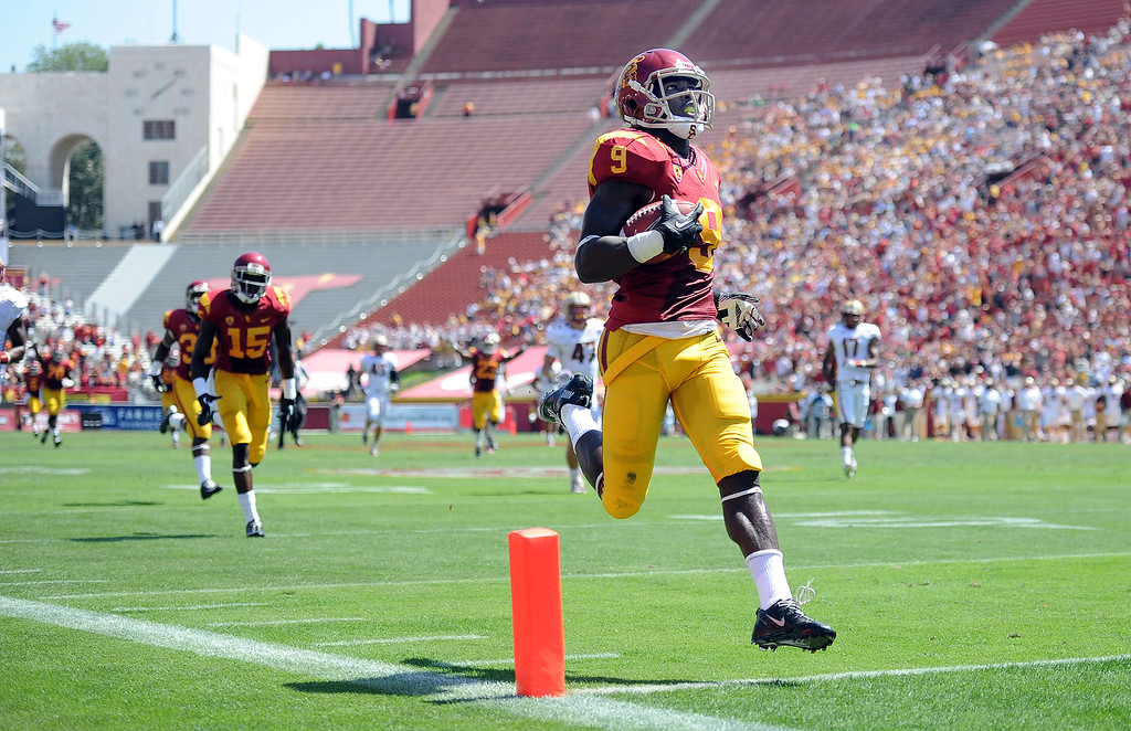 Description of . Southern California wide receiver Marqise Lee (9) catches a pass and runs for a 80 touchdown against Boston College during the first half of an NCAA college football game in the Los Angeles Memorial Coliseum in Los Angeles, on Saturday, Sept. 14, 2013.