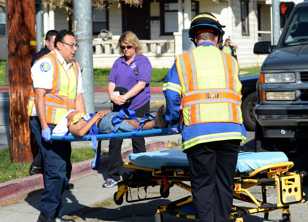 Description of . CARE Ambulance personnel prepare to transport a 12-year-old child that was struck by an SUV on Bailey Street and Pickering Avenue in Whittier on Thursday March 13, 2014. The child was then transported to a trauma center by a Los Angeles County rescue helicopter from Whittier High School. (Staff Photo by Keith Durflinger/Whittier Daily News)