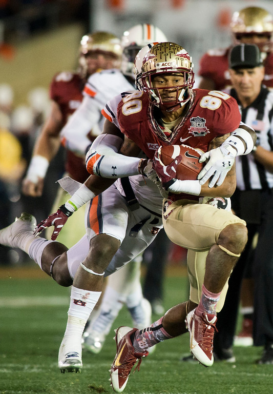 Description of . Florida's Rash Greene (80) runs with the ball past Auburn's Brandon Fulse (11) in the first half during the BCS National Championship game at the Rose Bowl in Pasadena Calif. on Monday, Jan. 6, 2014. (Watchara Phomicinda/ Pasadena Star-News)