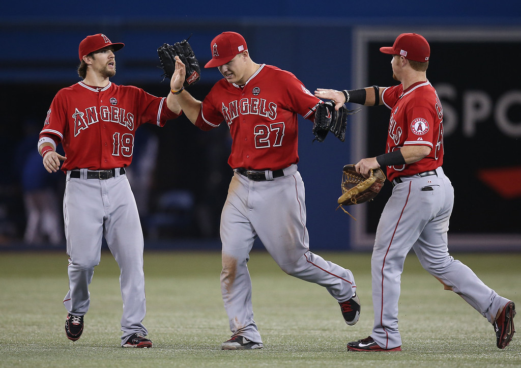 Description of . TORONTO, CANADA - SEPTEMBER 11: Mike Trout #27 (C) of the Los Angeles Angels of Anaheim celebrates their victory with Collin Cowgill #19 and Kole Calhoun #56 during MLB game action against the Toronto Blue Jays on September 11, 2013 at Rogers Centre in Toronto, Ontario, Canada. (Photo by Tom Szczerbowski/Getty Images)