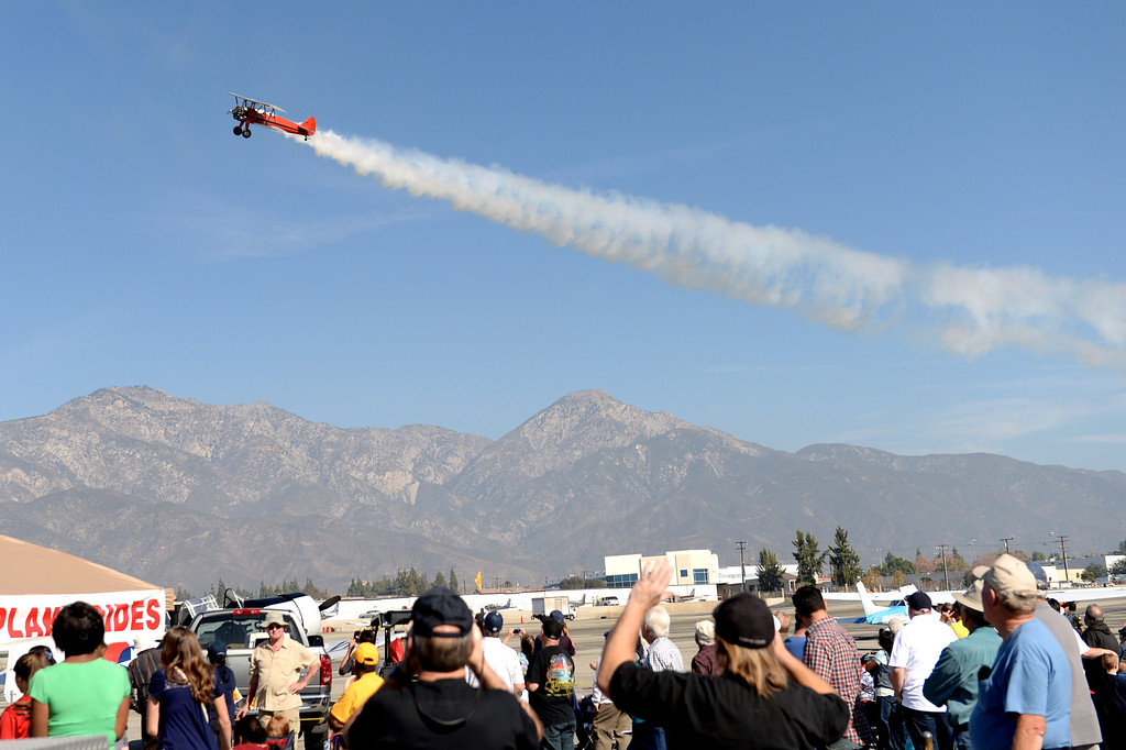 Description of . Spectators watch as an airplane performs aerobatics during the 39th annual Cable Airshow and Car Show at Cable Airport in Upland, Saturday, Jan. 11, 2014.(John Valenzuela/Staff Photographer)