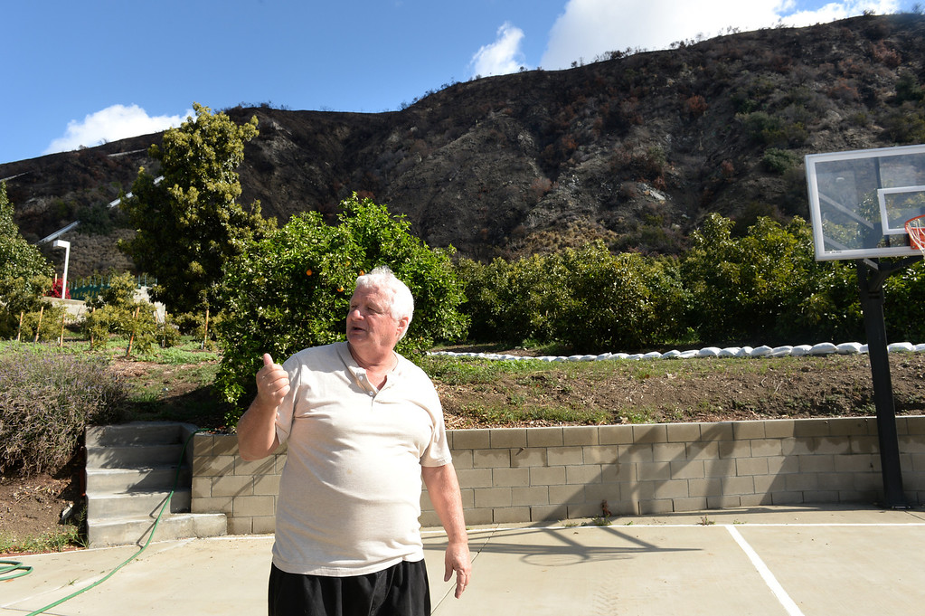 Description of . Ed Heinlein shows the hills behind his home on Ridge View Drive in Azusa that threaten to flood the homes with the next storm on Thursday February 27, 2014. (Staff Photo by Keith Durflinger/San Gabriel Valley Tribune)